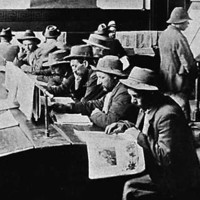 Image: A group of men in hats sit at two long tables and read newspapers