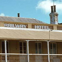 Image: Colour photograph of a two-storey late Victorian-era building on the corner of two paved streets. The building is painted tan with white columns and has the words 'Railway Hotel, 1849' painted beneath its roof