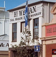 Image: Two elderly women stand in front of a brick-and-corrugated iron two-storey building. The words 'Hy. Weman. Sail Maker, Ship Chandler' are painted on the front of the building