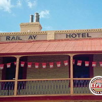 Image: Colour photograph of a two-storey late Victorian-era building on the corner of two paved streets. The building is painted tan with red trim and has the words 'Rail ay Hotel, 1856' painted beneath its roof