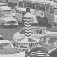 Image: A throng of auto-mobiles of 1940s, 1950s and 1960s vintage circle around a large plinth with the words 'Keep Left' painted on it