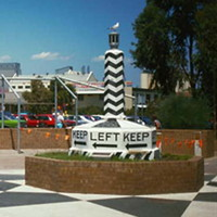Image: A large plinth painted with an alternating black and white pattern, and emblazoned with the words 'Keep Left' and directional arrows at its base, is displayed in a park area made of brick