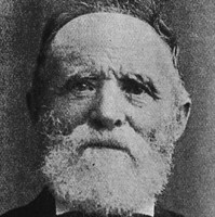 Image: A photographic head-and-shoulders portrait of an elderly Caucasian man with a white beard. He is wearing a late nineteenth century suit with bowtie