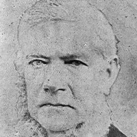 Image: A photographic portrait of a middle-aged man with white hair and large, mutton-chop sideburns