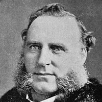 Image: A photographic head-and-shoulders portrait of a Caucasian man with large mutton-chop sideburns wearing late Victorian-era clothing, including an overcoat with fur collar