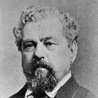 Image: A photographic head-and-shoulders portrait of a middle-aged Caucasian man with curly salt-and-pepper hair and goatee. He is wearing a late nineteenth-century suit and tie