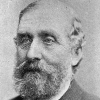 Image: A photographic head-and-shoulders portrait of a bearded middle-aged man in a tweed suit with tie