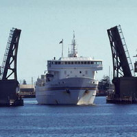 Image: A large, modern steel-hulled ferry passes through an open drawbridge. Part of a wharf is visible in the foreground