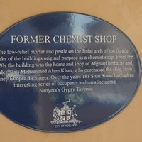 Image: blue, oval plaque with white writing on yellowy-beige wall