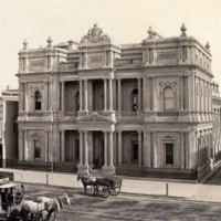 Image: horse carts and tram in front of ornate bank building