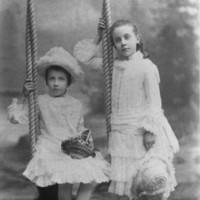 Image: Two young girls pose for a portrait. One sits on a swing, the other stands beside her. They are wearing white, frilly dresses.