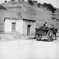 Image: Horse and cart in front of run-down toll house building