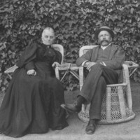 Image: A man and a woman sit outside in wicker chairs