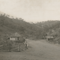 Image: Children standing on road with hills and toll house