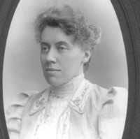 Image: Portrait photograph of a woman facing slightly side on. The photograph itself is an oval shape