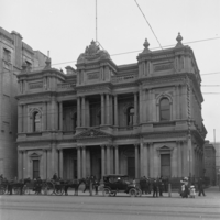 Image: horse carts and car in front of ornate bank building