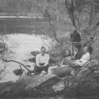 Image: Three women and two boys have a picnic on the banks of a river.