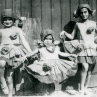 Image: Three girls in costume with pom-poms attached to skirts