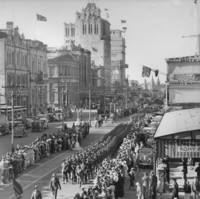 Image: Military parade down a main street, with tall buildings in the background
