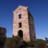 Image: Front view of a tall ruined building surrounded by small bushes