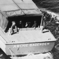 Image: A boat with a group of children sitting in the stern travels along a waterway. Two policemen are visible standing at midships on the starboard side