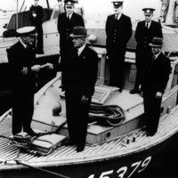 Image: Six men stand on the bow of a boat. One man in a naval uniform passes a paper document to another man in a civilian suit