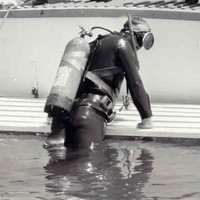 Image: A scuba diver exits the water at the stern of a small motor boat. Two police officers aboard the boat look on