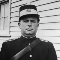 Image: A man in a police uniform with kepi cap and leather bandolier