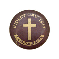Image: purple badge with cross and white text