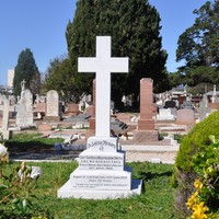 Image: large white cross surrounded by garden and other graves