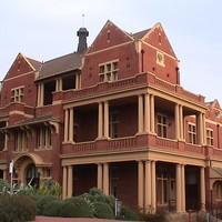 Image: Modern photograph of a large red brick building with yellow painted decorative details such as columns, and featuring a verandah and balconies.