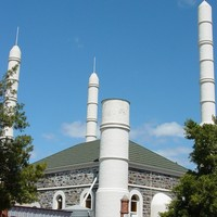 Image: A grey stone building bracketed by three minarets