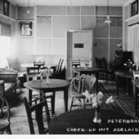Image: Black and white image of the Peterborough room inside the Cheer up hut. The image shows a piano in the right far corner and a semi circular seat in the far left corner. Also in the room are dining settings and lounges.
