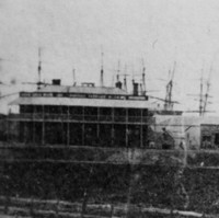Image: A large paddock, behind which is a large complex of long, single-storey late Victorian-era stone buildings with steam trains parked in front of them. A two-storey building and several ship masts are visible in the distant background