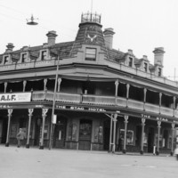 Image: A large three storey corner hotel with a second floor balcony also forming a verandah and gable windows.