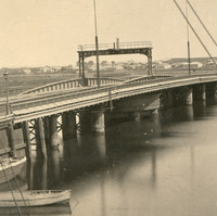 Image: A nineteenth-century swing bridge with centrally located turntable extends across a narrow river. A number of small sailing craft are visible in the river next to the bridge
