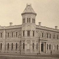 Image: A large, two-storey stone building in Victorian Italianate style. One corner of the building features an octagonal tower with an additional storey
