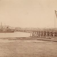 Image: A large iron and wood bridge under construction. Both approaches are nearing completion, while the central span is yet to be started. A barge with cranes is moored in the river near the bridge