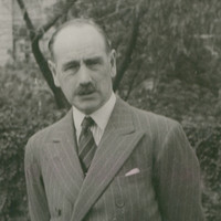 Image: A balding, moustachioed, middle-aged Caucasian man in a 1940s-era suit poses for a photograph with his wife and two young children. One child is a boy, and the other is a girl