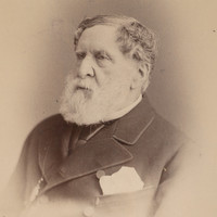 Image: a photographic head and shoulders portrait of an elderly bearded man in three-quarter profile.