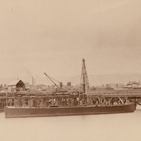 Image: An iron and wooden bridge under construction extends across a narrow river. A nineteenth century sailing vessel and a couple of buildings are visible in the background. A wooden-hulled barge with a derrick is moored next to the bridge