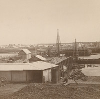 Image: A bridge under construction extends across a narrow river. A narrow wooden footbridge is located to the left of the bridge that is being built. Several nineteenth century buildings are visible in the distant background