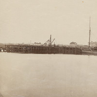 Image: The approaches to a large wooden and iron bridge are in the process of being built. A section of river containing a number of nineteenth century sailing ships are visible in the right foreground