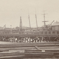 Image: A wooden footbridge extends across a river. A handful of nineteenth-century buildings and sailing ships are visible in the background