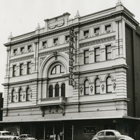 Image: a four storey building with highly decorative facade and plain brick sides. A large arch surrounds a balcony in the centre of the facade and the entrance is protected by a verandah. 1960s era cars are parked outside.