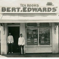 Image: Two men stand in the doorway of a small shop building. A sign on the roof of the shop reads 'Tea Rooms, Bert.Edwards'
