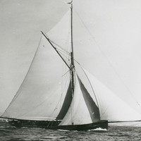 Image: A small, single-masted sailing vessel with a cutter rig under-way with a full press of canvas. A shoreline with white sandy beach is visible in the distant background