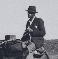 Image: A young Caucasian man rides a camel in the Australian outback. He is dressed in 1930s attire, including a fedora hat