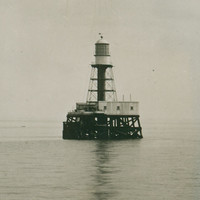 Image: A metal lighthouse with a large wooden support platform stands surrounded by water. Large steam- and sail-powered ships are visible in the distant background