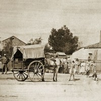 Image: horse and cart on dirt street with group of people, including young children, surrounding